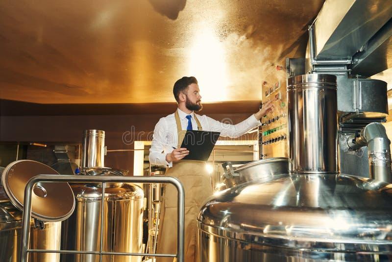 Hübscher Ingenieur der Brauerei Brauprozess kontrollierend stockfotografie