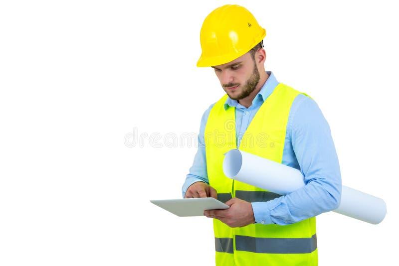Hübscher Ingenieur, der mit einem Tabletten-PC, lokalisiert auf Weiß arbeitet stockbild