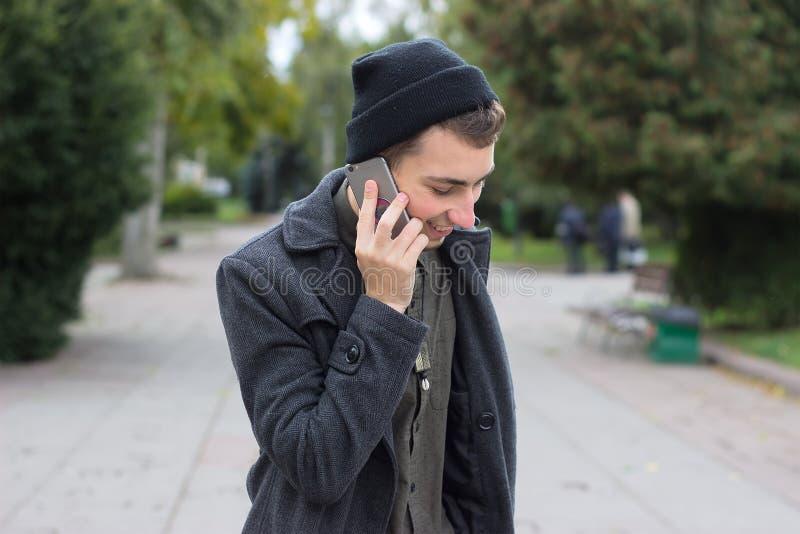 Hübscher Jugendlicher, der an einem Handy spricht lizenzfreies stockfoto