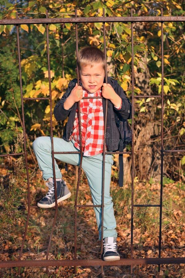 Hübscher Junge in den Jeans klettert auf Eisengitterzaun stockbilder