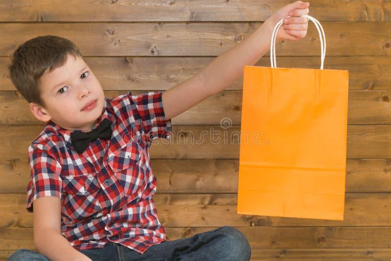 Hübscher Junge, der in der Hand eine Geschenktasche auf einem hölzernen Wandhintergrund hält lizenzfreie stockfotos