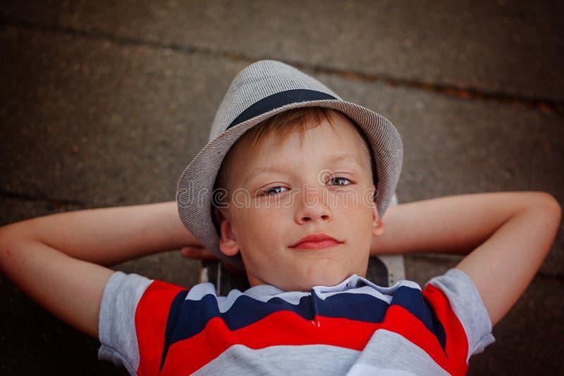 Hübscher Junge des Nahaufnahmeporträts im Hut, der auf Skateboard im Sommer liegt stockfotografie