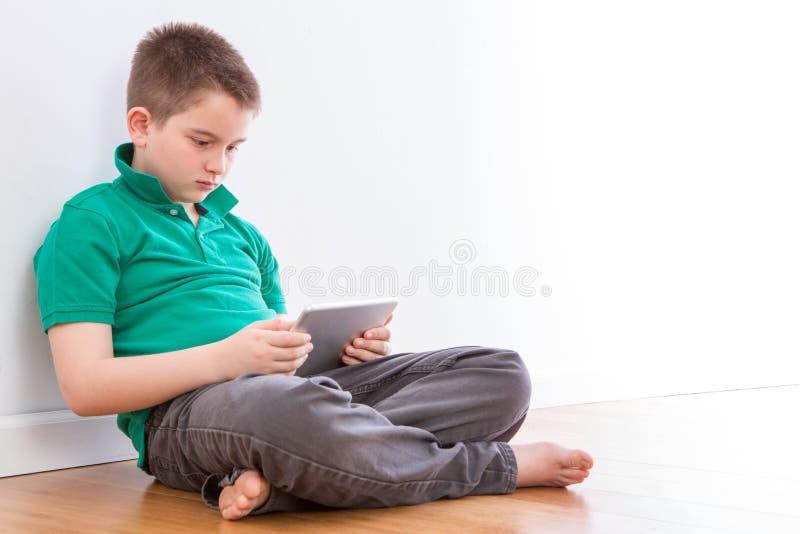 Hübscher Junge mit dem Tablet, das auf Wand sich lehnt lizenzfreies stockbild