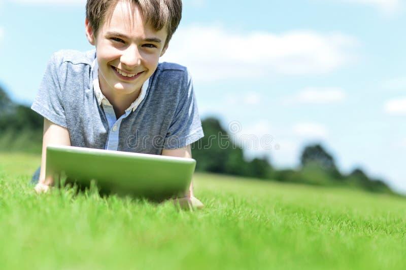 Hübscher Junge mit Tablettengerät, draußen stockfotos