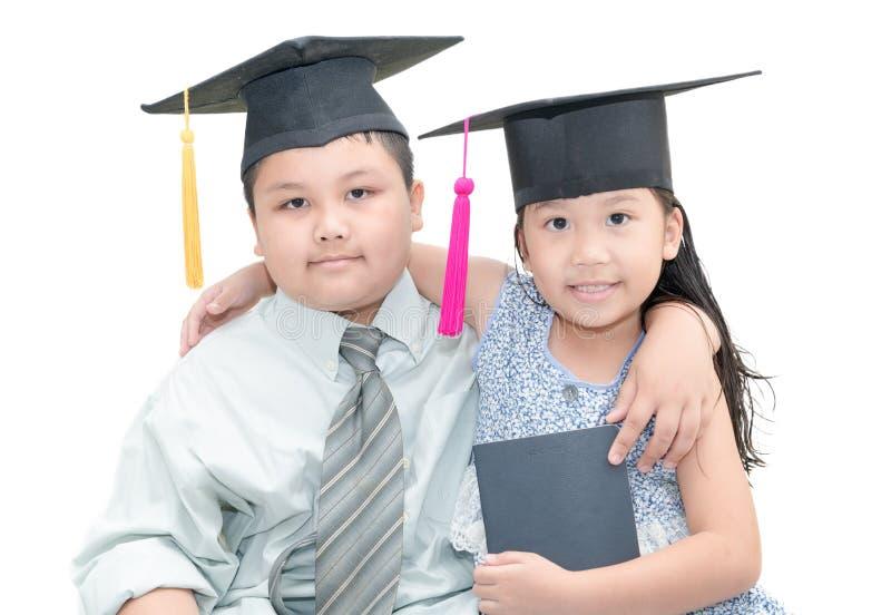Hübscher Junge und nettes Mädchen mit graduierter Kappe stockfotos