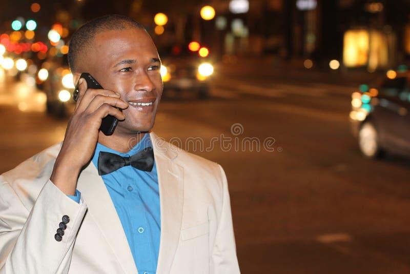 Hübscher junger afrikanischer Mann, der am Handy in der Nachtstadt spricht lizenzfreie stockfotos