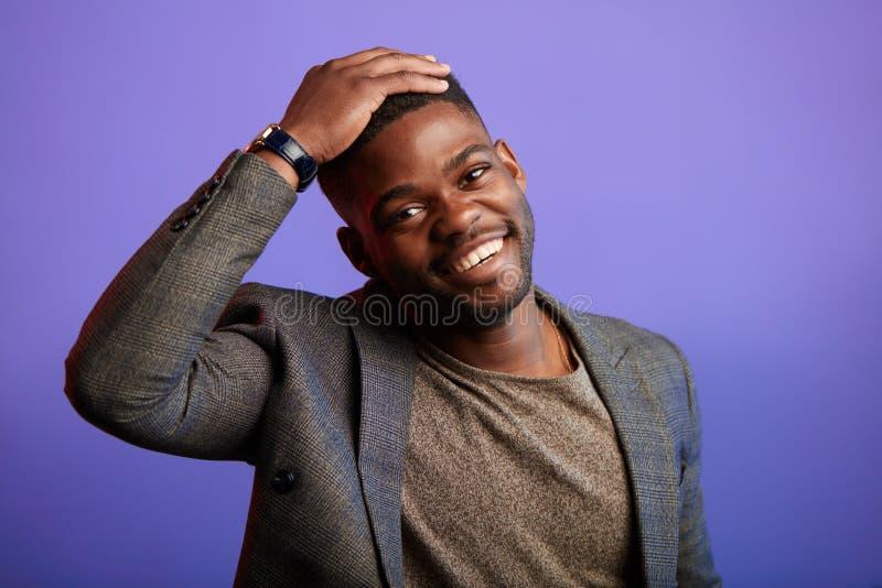 H?bscher junger afrikanischer Mann in der intelligenten zuf?lligen Jacke l?chelnd ?ber purpurrotem Hintergrund lizenzfreie stockfotos