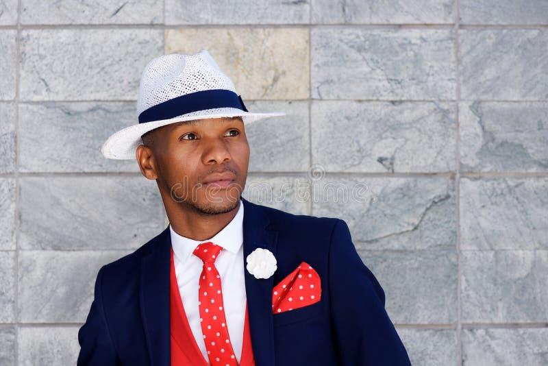Hübscher junger afrikanischer Mann im Anzug und in Hut, die weg schauen lizenzfreies stockfoto