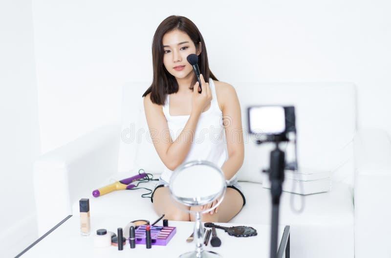 Hübscher junger Asiatin Blogger, der Bürste für verwendet, bilden das Zutreffen Prozess von ein Video über Make-upschönheit  lizenzfreies stockbild