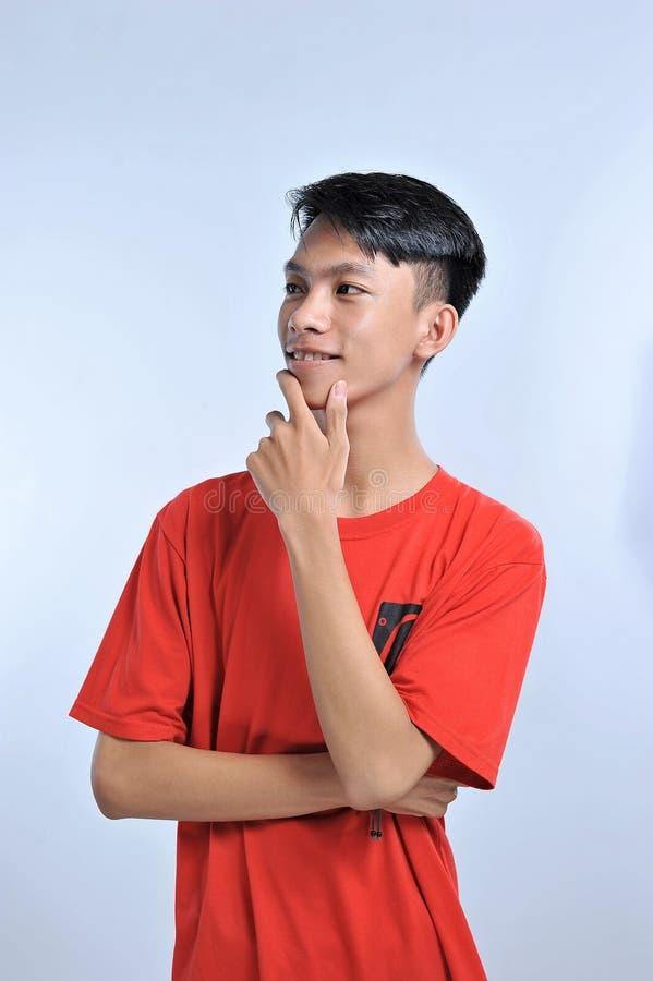 Hübscher junger asiatischer Junge, der orange T-Shirt mit der Hand auf dem Kinn denkt an Frage, nachdenklicher Ausdruck trägt L?c stockfotografie