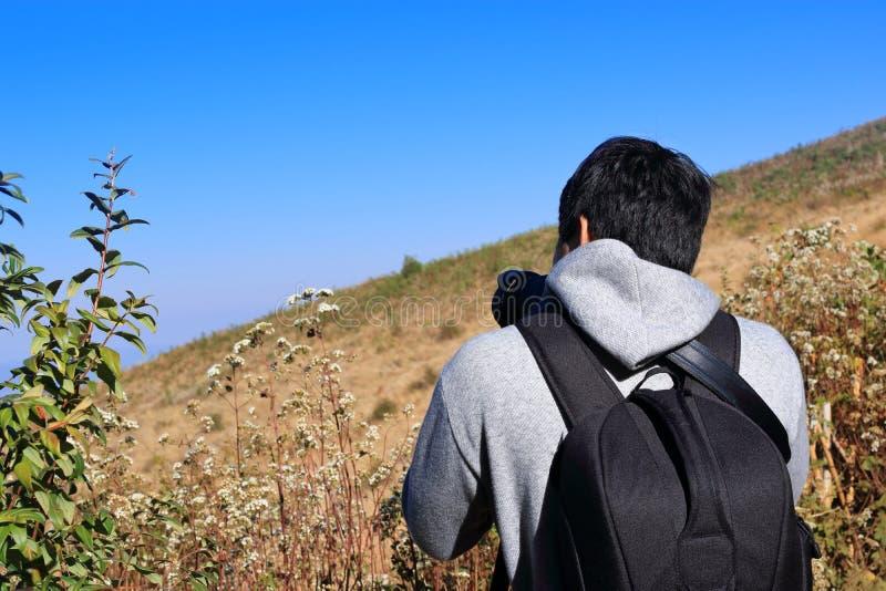 Hübscher junger asiatischer touristischer Mann, der Foto mit dslr Kamera an Naturlehrpfad Kew Mae Pan bei Doi Inthanon, Chaingmai stockbilder