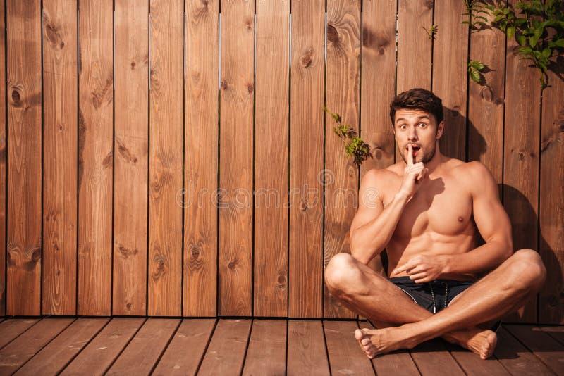 Hübscher junger aufgeregter Mann, der Ruhegeste sitzt und zeigt stockfoto