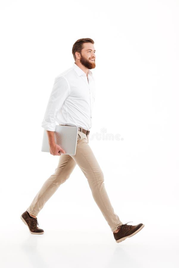 Hübscher junger bärtiger Mann, der über weiße Wand geht stockfotografie