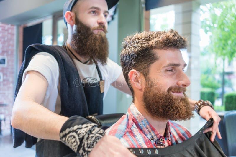 Hübscher junger bärtiger Mann, der ein lächelt modisches haircu vorher, habend stockfotos