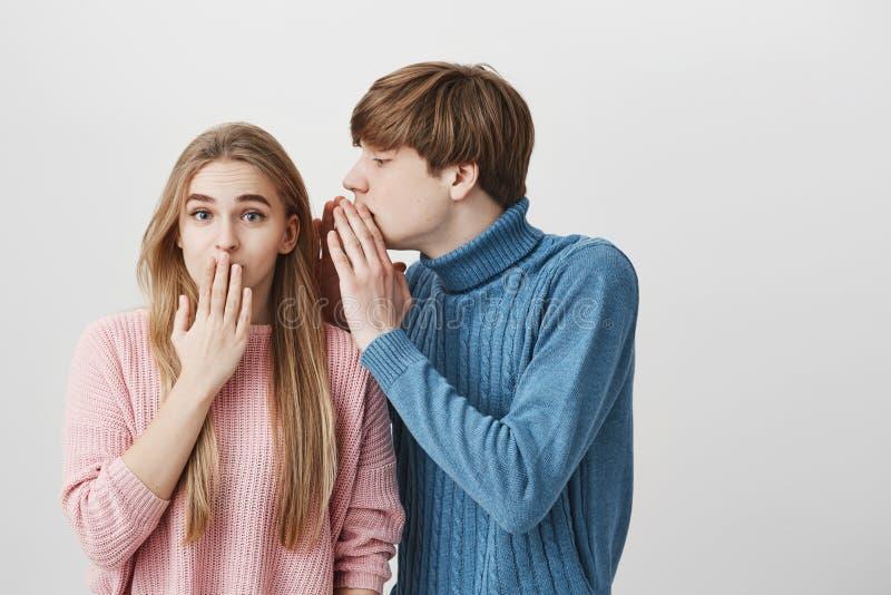 Hübscher junger blonder männlicher Student in der blauen Strickjacke, etwas in das Ohr des stilvollen blonden Mädchens flüsternd  lizenzfreie stockbilder