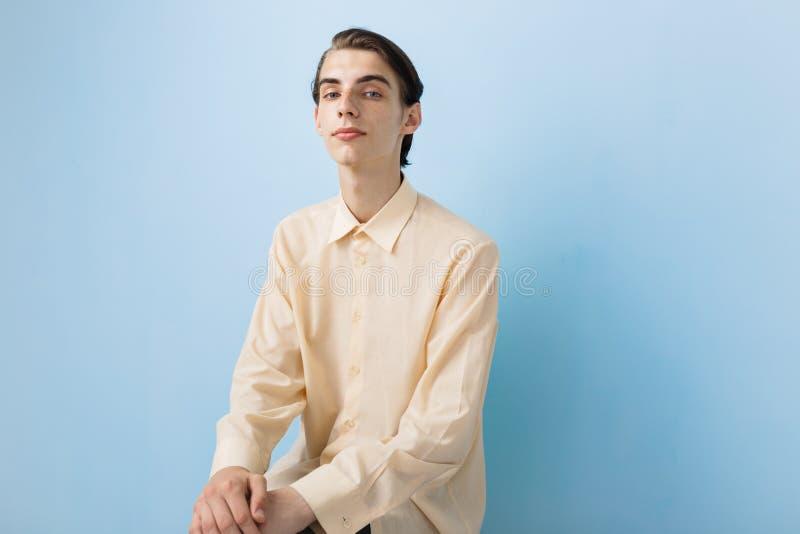Hübscher junger dünner dunkelhaariger Kerl mit den blauen Augen, die das gelbe Hemd aufwirft über blauer Wand tragen stockfoto