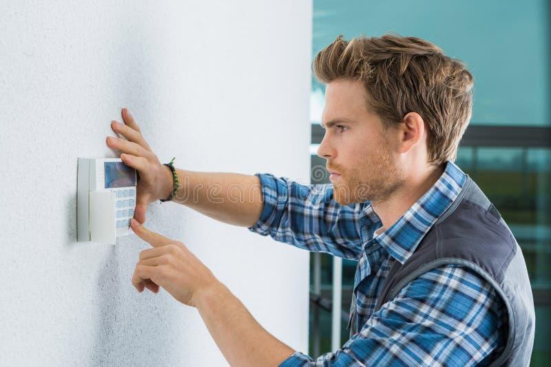 Hübscher junger Elektriker, der Wechselsprechanlage repariert lizenzfreie stockbilder