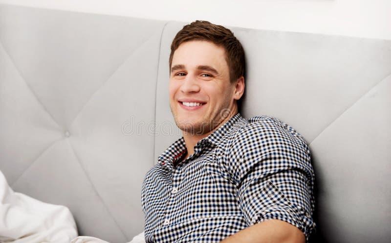 Hübscher junger erwachsener Mann im Schlafzimmer lizenzfreie stockfotografie