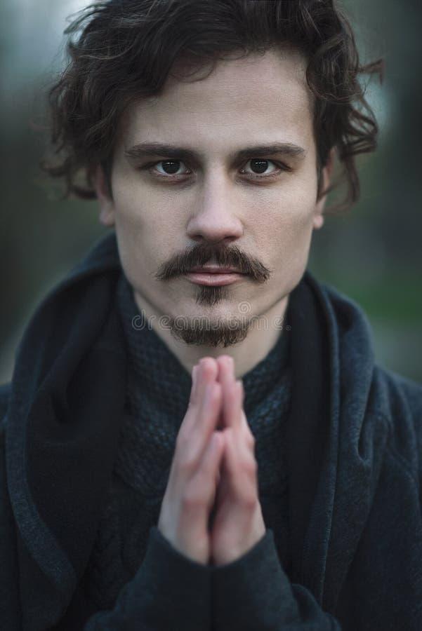 H?bscher junger gelockter herzlichst betender Mann Buch und Kreuz lizenzfreies stockfoto