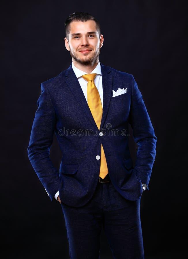 Hübscher junger Geschäftsmann, der auf Schwarzem steht lizenzfreie stockbilder