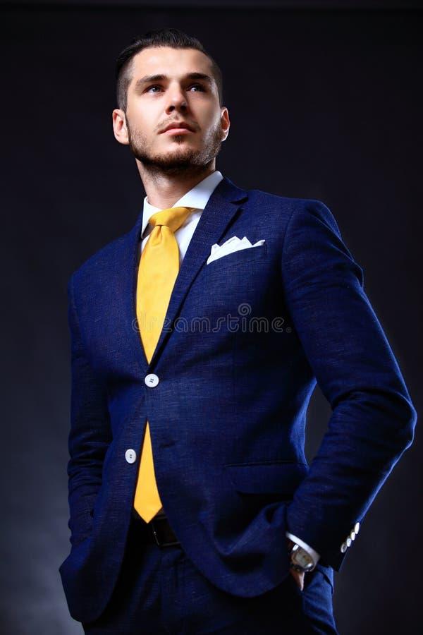 Hübscher junger Geschäftsmann, der auf Schwarzem steht lizenzfreie stockfotos