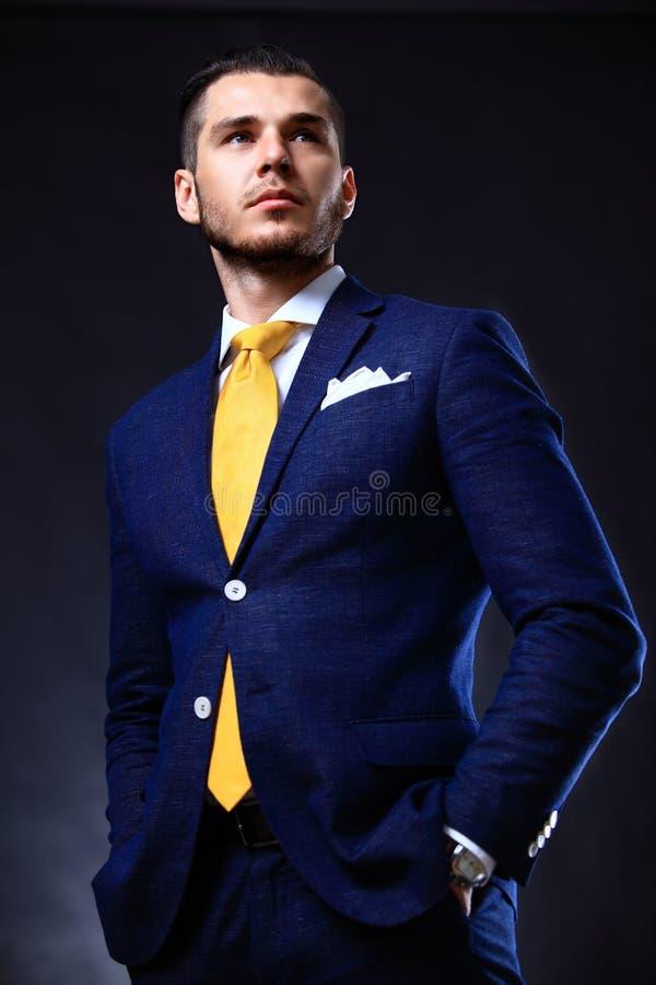 Hübscher junger Geschäftsmann, der auf Schwarzem steht stockfoto
