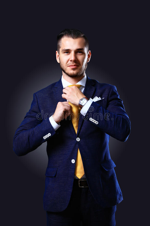 Hübscher junger Geschäftsmann, der auf Schwarzem steht stockfotografie