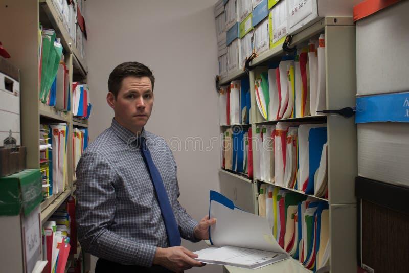 Hübscher junger Geschäftsmann, der Dateien sucht lizenzfreies stockbild