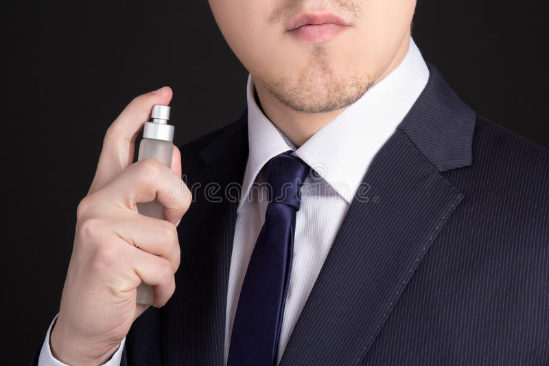 Hübscher junger Geschäftsmann, der Parfüm verwendet stockfoto