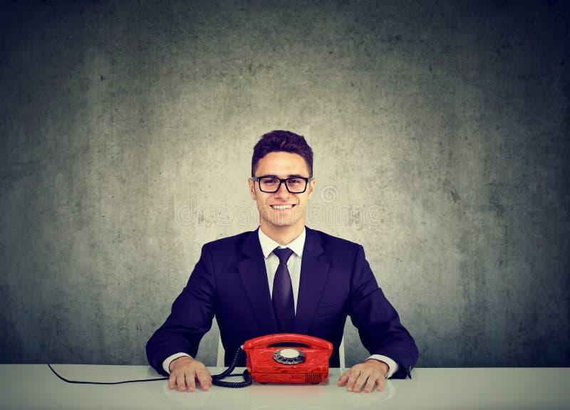 Hübscher junger Geschäftsmann, der am Schreibtisch mit Weinlesefestnetztelefontelefon sitzt lizenzfreie stockfotos