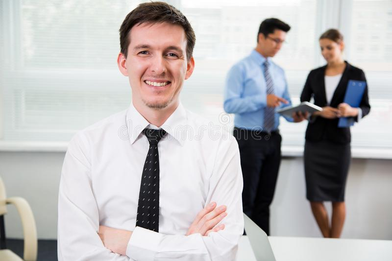 Hübscher junger Geschäftsmann im Büro lizenzfreie stockfotografie