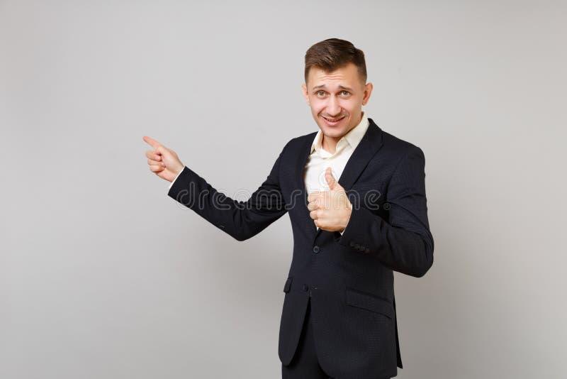 Hübscher junger Geschäftsmann im klassischen schwarzen Anzugsvertretungsdaumen oben, die Zeigefinger zeigend beiseite lokalisiert lizenzfreie stockfotos