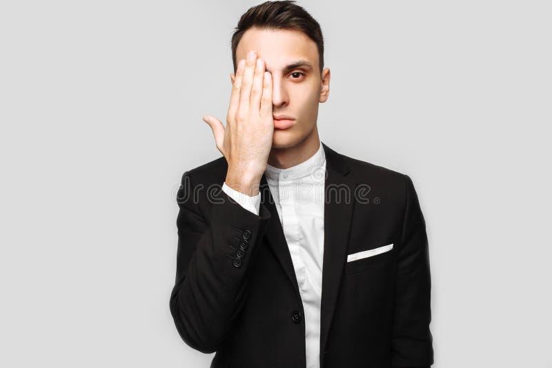 Hübscher junger Geschäftsmann, Mann, in einem klassischen schwarzen Anzug, Show lizenzfreie stockfotografie