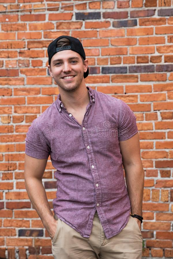 Hübscher junger kaukasischer Mann mit Mobiltelefon und rückwärts Hut lächelnd für Porträts vor strukturierter Backsteinmauer-Auße stockbilder