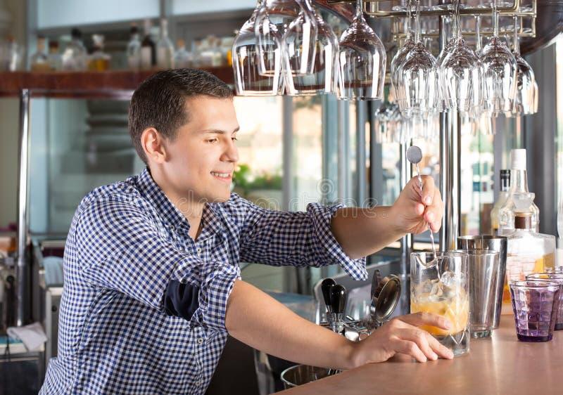 Hübscher junger lächelnder Barmixer, der einen Esprit des alkoholischen Getränks rührt stockfoto