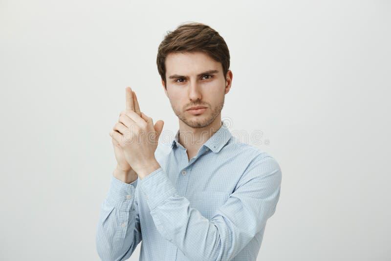 Hübscher junger männlicher Büroangestellter, tragendes formales Hemd und Herstellung der Gewehrgeste, Hände anhebend, als ob es W stockfoto