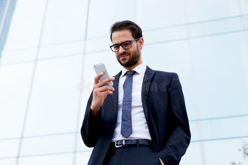 Hübscher junger Manager einer großen Gesellschaft ist in den Händen des Telefons und des Lächelns lizenzfreies stockfoto