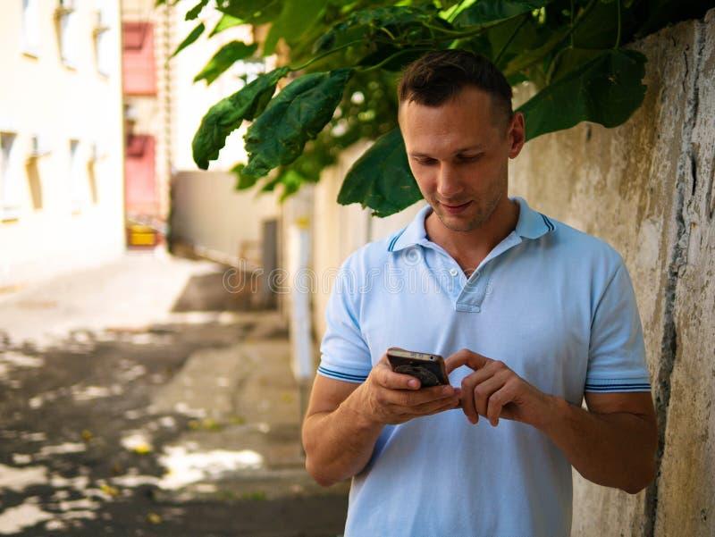 Hübscher junger Mann über weißem Wandhintergrund plaudernd durch den Handy, der beiseite schaut stockfoto