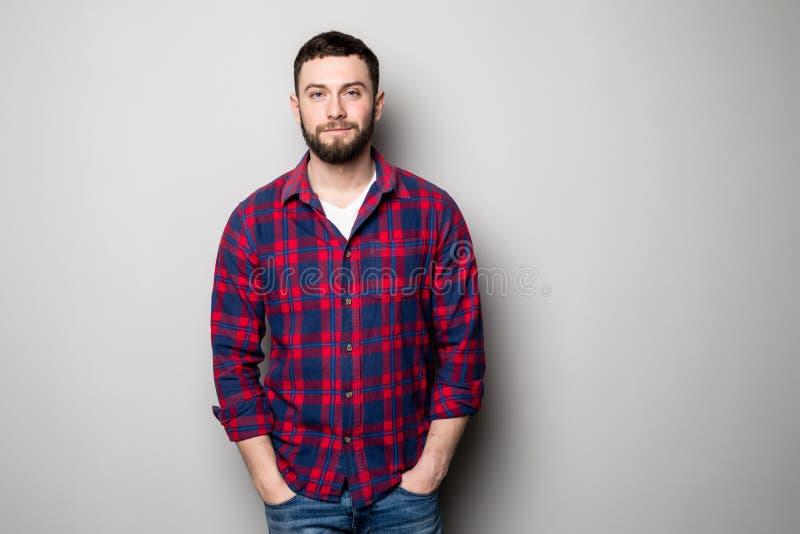Hübscher junger Mann auf dem grauen Hintergrund, der Kamera betrachtet Porträt des Lachens des jungen Mannes mit den Händen in de stockbilder