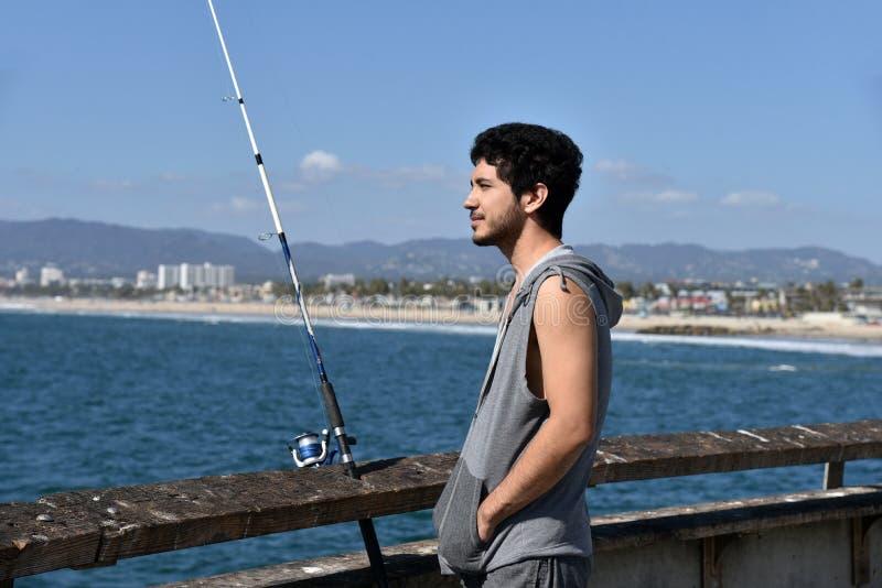 Hübscher junger Mann auf einem Fischenpier stockbilder