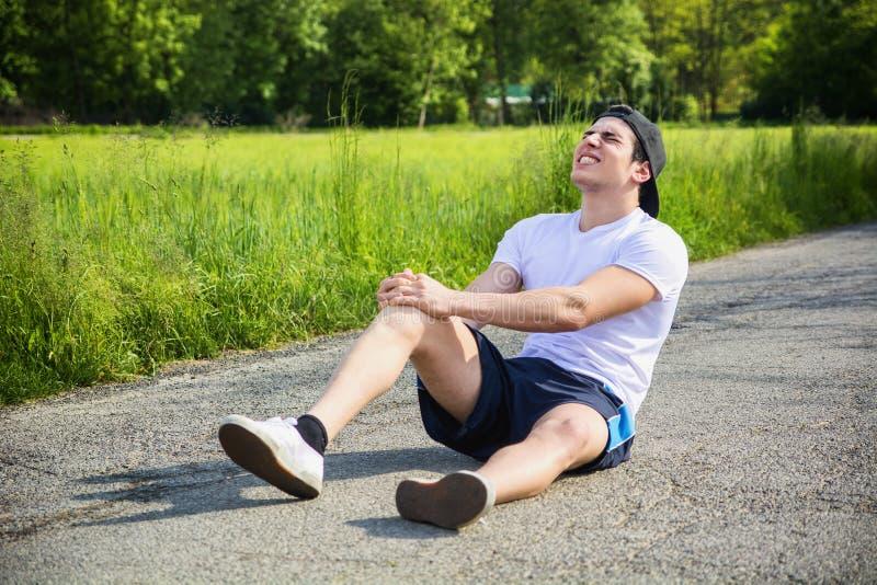Hübscher junger Mann beim Laufen verletzt und stockbild