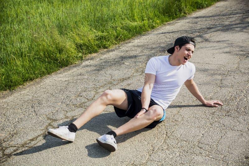 Hübscher junger Mann beim Laufen verletzt und stockbilder