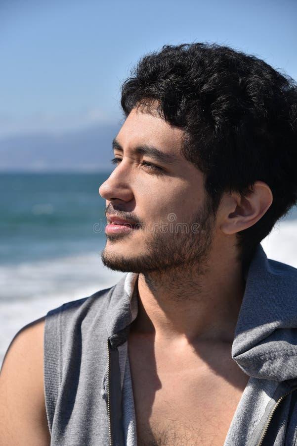 Hübscher junger Mann, der über dem Ozean schaut stockfotografie