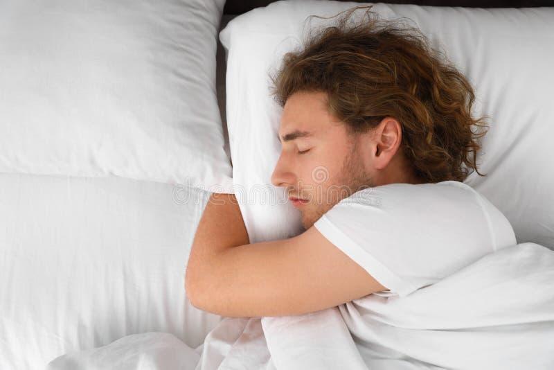 Hübscher junger Mann, der auf Kissen, Ansicht von oben mit Raum für Text schläft lizenzfreies stockfoto