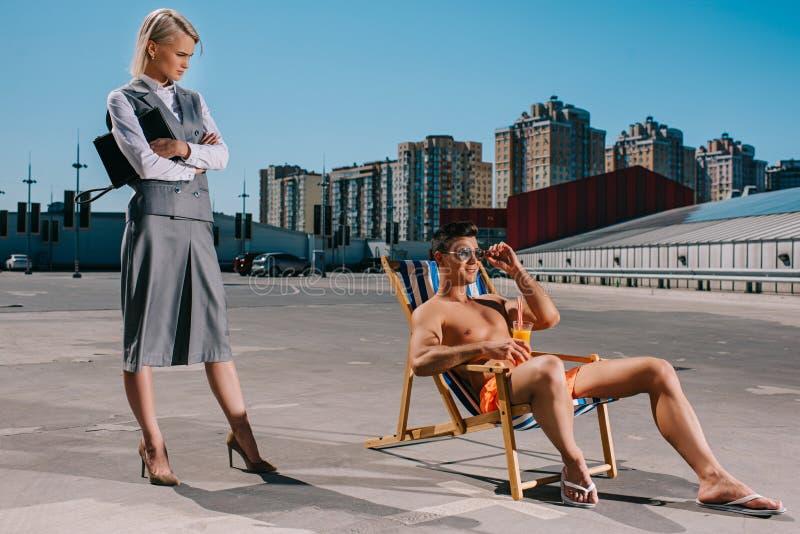 hübscher junger Mann, der auf Sonnenruhesessel während sein Damenchef in der Klage steht nahe bei ihm mit den gekreuzten Armen si lizenzfreies stockbild