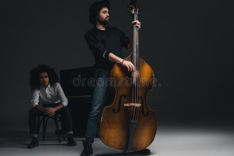 hübscher junger Mann, der Cello während sein Partner sitzt am Klavier verwischt spielt stockbilder