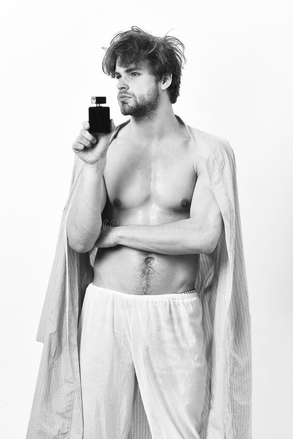 Hübscher junger Mann, der das Parfüm lokalisiert auf weißem Hintergrund verwendet lizenzfreie stockfotos