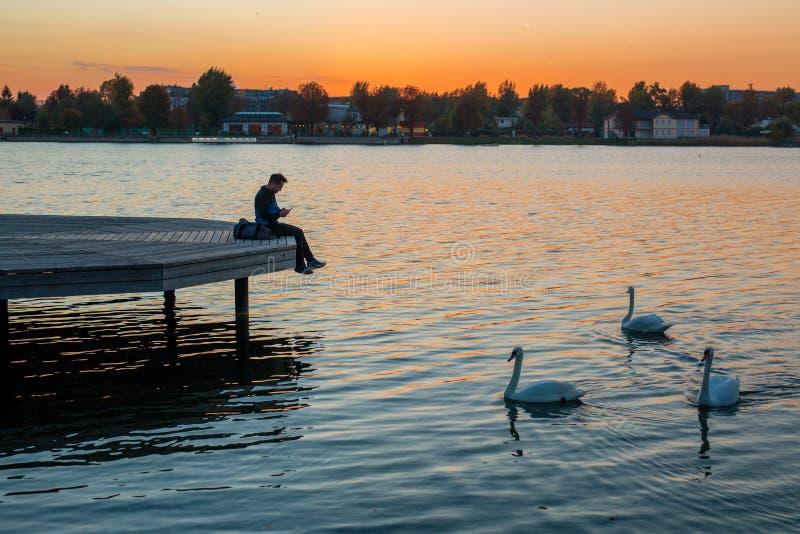 Hübscher junger Mann, der den Sonnenuntergang auf der Ufergegend während t genießt lizenzfreie stockfotos