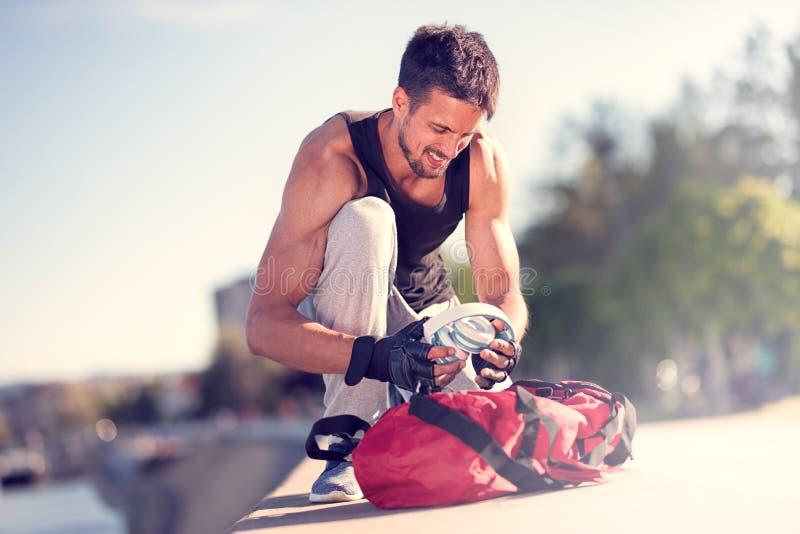 Hübscher junger Mann, der die laufende Ausrüstung vorbereitet lizenzfreie stockfotos