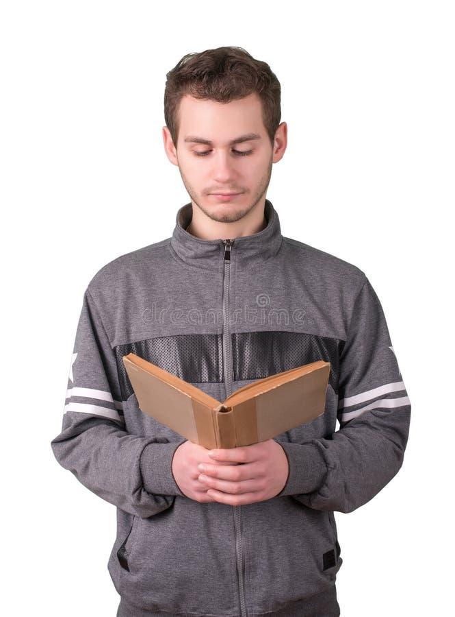 Hübscher junger Mann, der ein altes Buch auf weißem Hintergrund liest stockfotos
